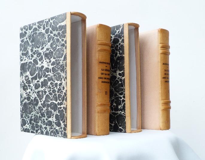 Deux volumes de ce livre culte chez les bretons. Plein-cuir beige, dos passé, mosaique simple, non cernée, représentant l'Ankou, personnage traditionnel en Bretagne qui vient avec sa faux et sa charettes chercher les morts.