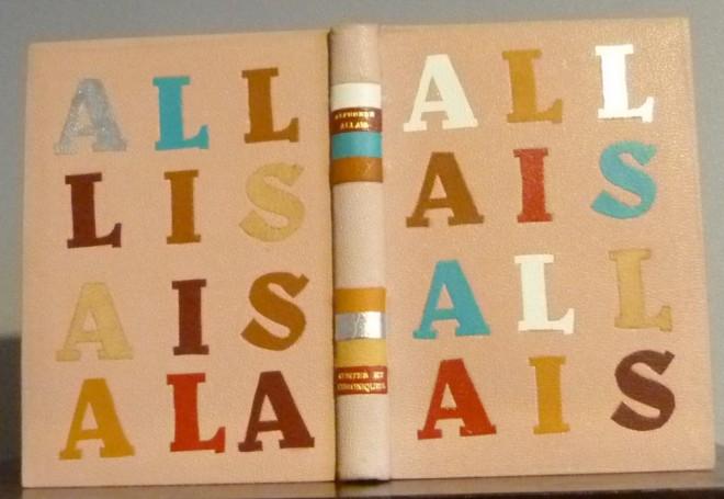Plein cuir rose, plats mosaïqués de lettres de différentes couleurs formant le nom de l'auteur