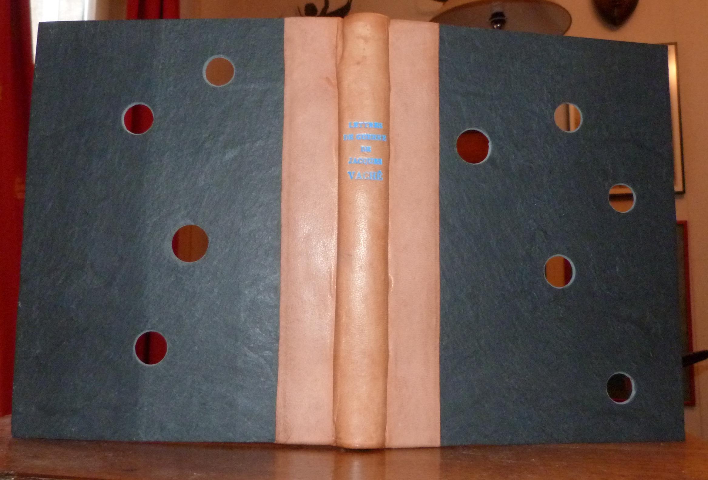 Demi-cuir beige clair, plats en ardoises percées de trous faisant apparaitre des fragments de couverture