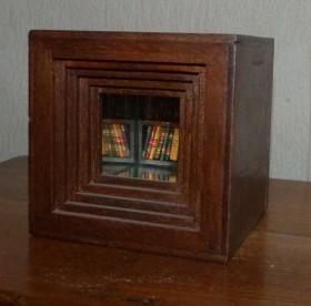 Cube en bois de 10cm de côté contenant en son fond une bibliothèque de 40 minis-livres