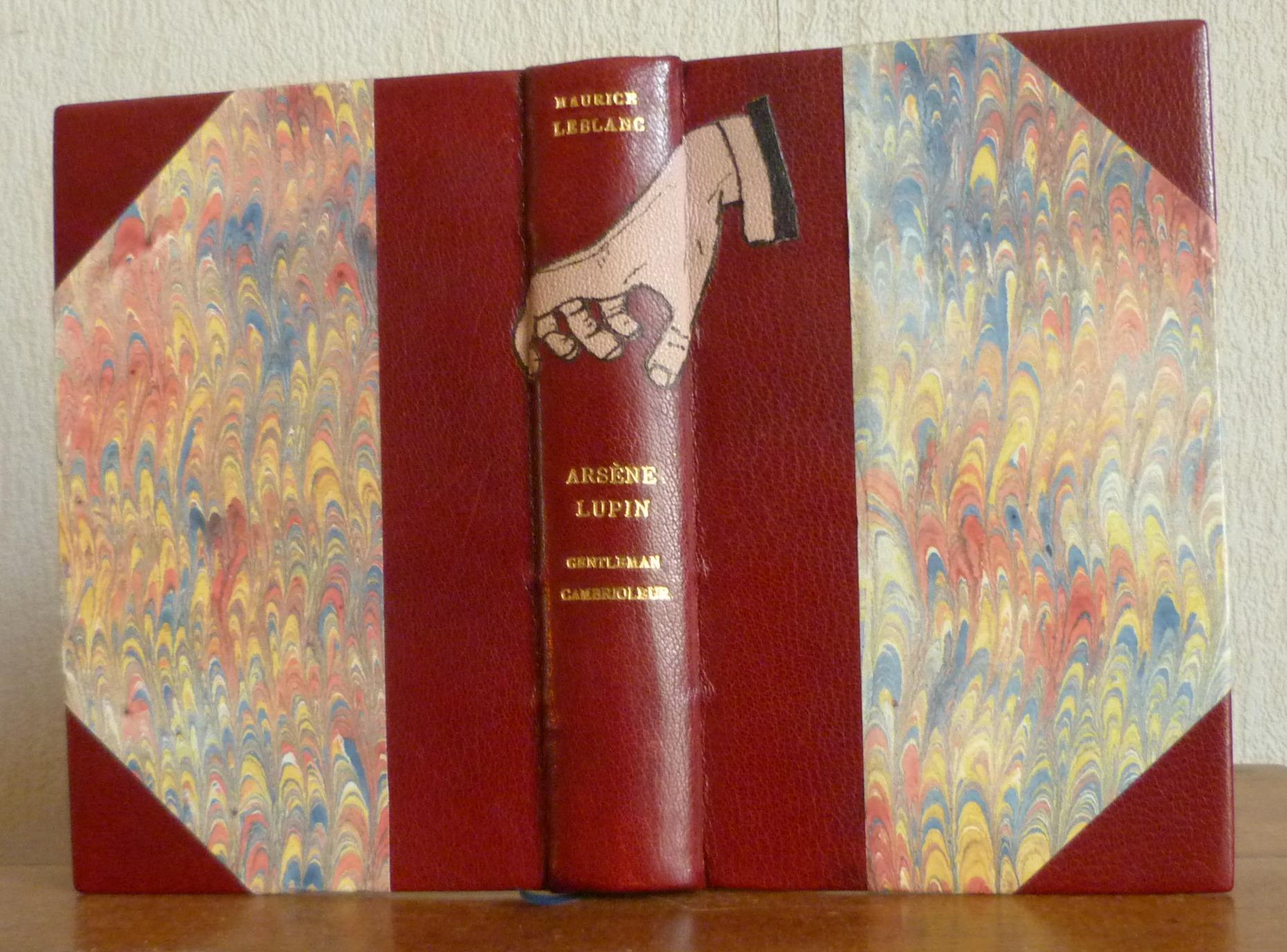 Demi-cuir à coins bordeaux, mosaïques sur le dos du livre reprenant une partie de la couverture du livre