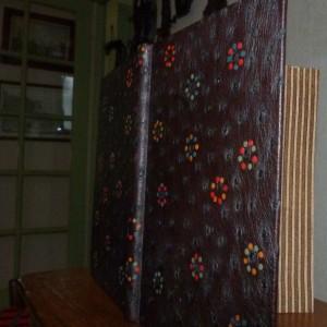 plein cuir d'autruche bordeau foncé, incrustations de cercles formés de petits disque multicolores