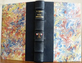 Demi cuir bleu, cinq nerfs, mosaïques représentant deux drapeaux français croisés entre le nerf 3 et le nerf4, tranchefile bleu, blanc et rouge.