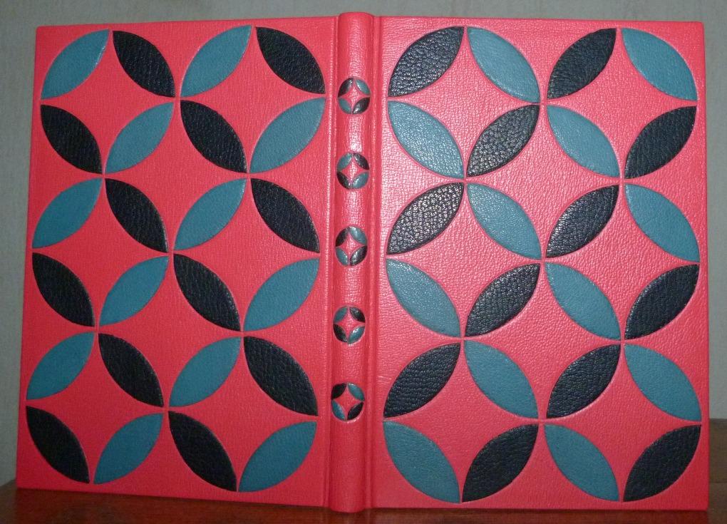 Bradel plein cuir rouge ornés d'arc de cercles, formant des cercles,noirs et bleus