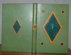 Plein cuir vert orné d'un l'osange et de 4 disques en galuchat vert, cernés de cuir de patte d'autruche jaune, sur chaque plat.Bradel.