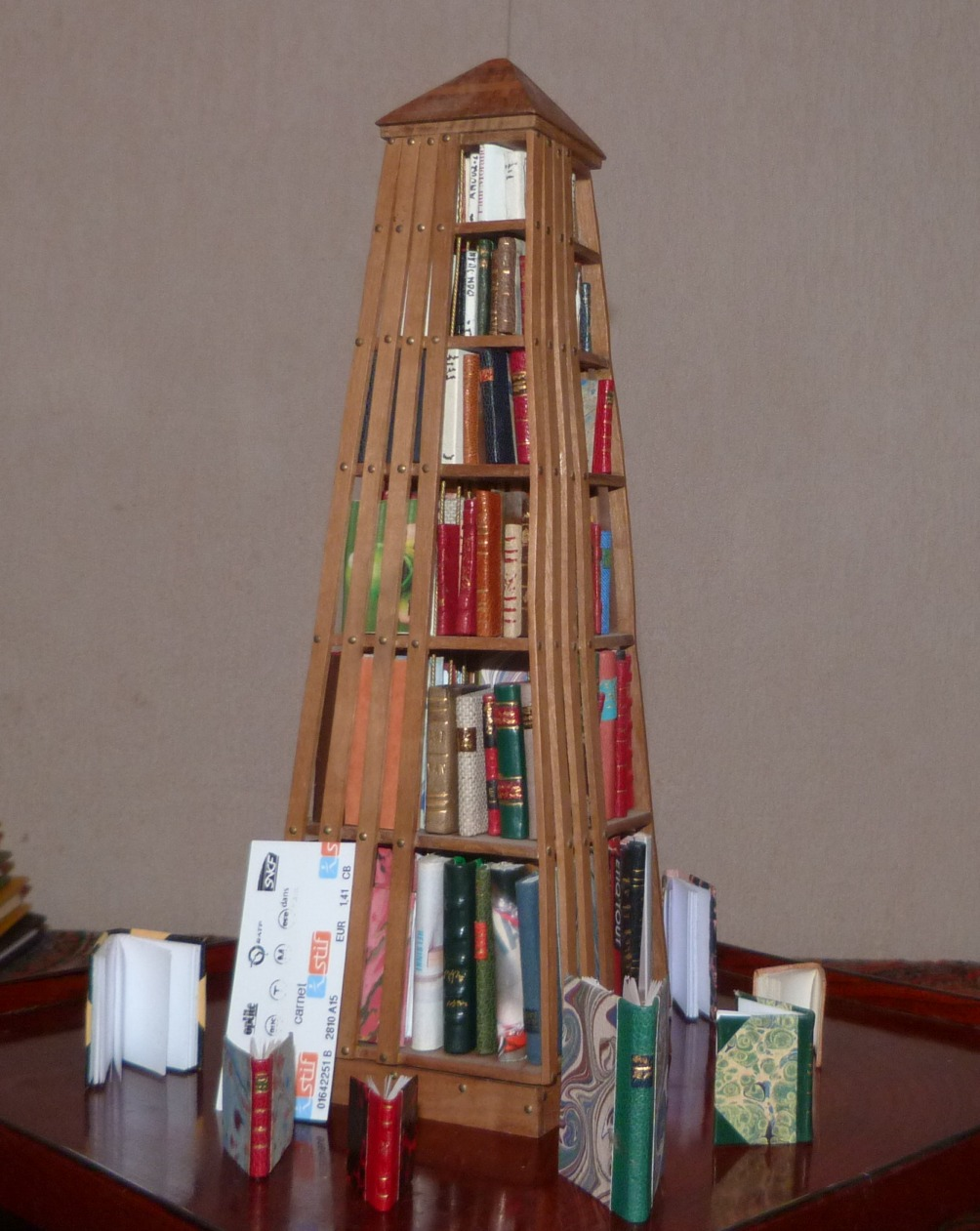 Mini bibliothèque pyramidale, à base carrée de 27cm de haut comprenant environ 140 livres tous différents sur 6 niveaux