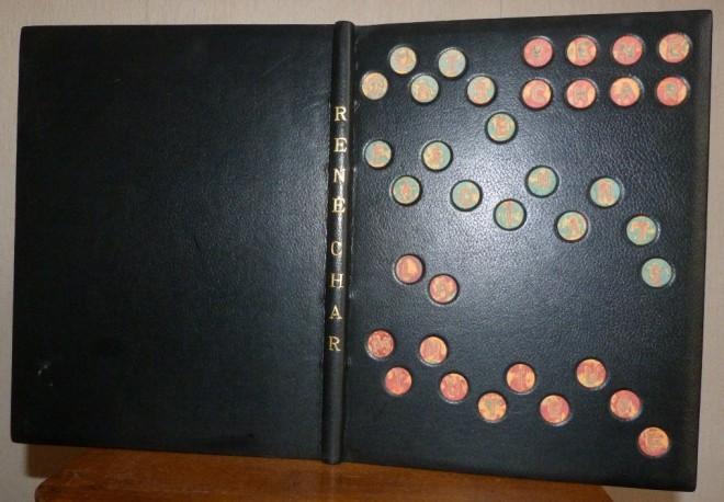 Plein cuir noir, titre à la chinoise, incrustation sur le plat antérieur de disque de papiers craft de différentes couleurs, superposés puis poncés faisant lettres du titre et de l'auteur.
