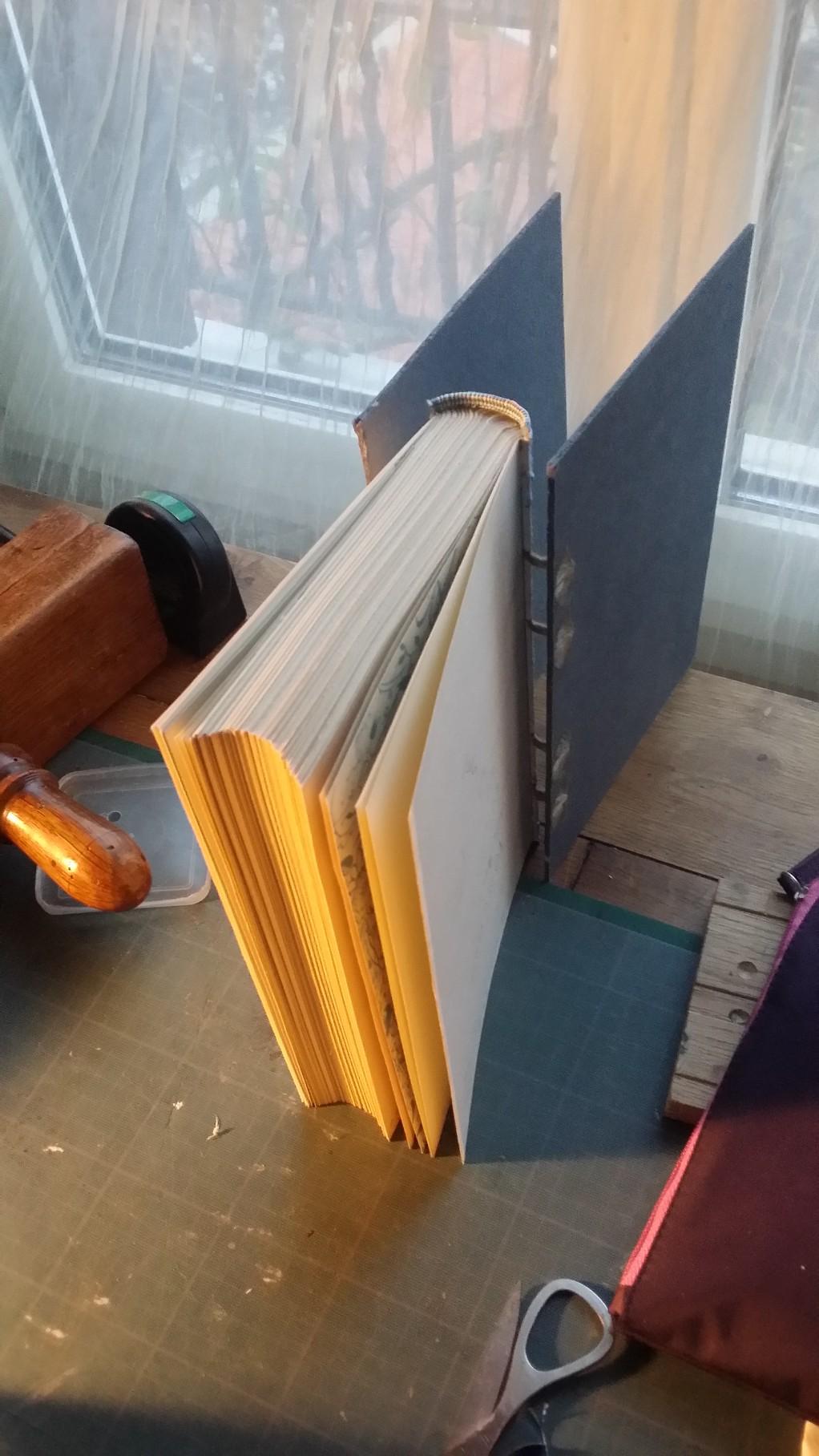 Vues d'un livre en cours de reliure, après la pose de la tranchefile et avant la pose des papiers kraft.