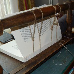 livre en cours de couture sur un cousoir.