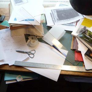 Bureau en désordre : amas de feuilles, règles, ciseaux