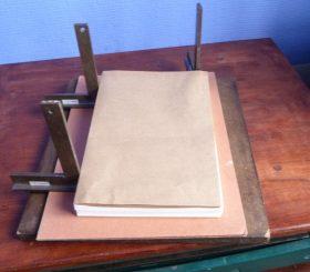 Cahier de papier kraft déposé sur une reliure en cours de fabrication
