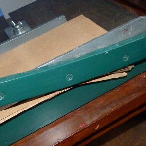 Cisaille de reliure de couleur verte lors de la découpe de papier Kraft