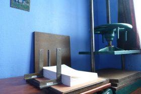Atelier du relieur : vue des feuillets calés avec des équerres devant la presse, vide