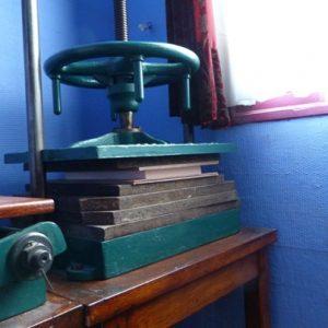 Atelier du relieur : vue des feuillets mis sous presse entre des planches de bois