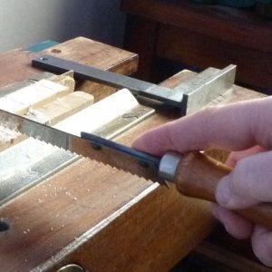 La main du relieur tient fermement la scie à main afin de scier le dos du livre de manière nette