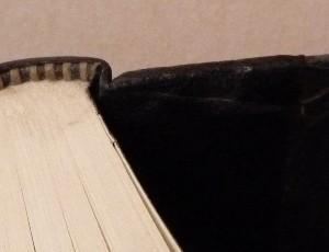 Demi-cuir noir, plats en ardoise, mosaïque en cuir noir et blanc représentant Figaro, 4 nerfs.