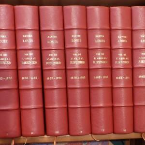 7 tomes reliés identiquement, demi-cuir à coins, rouge, papier Annonay rouge. Poisson d'avril.