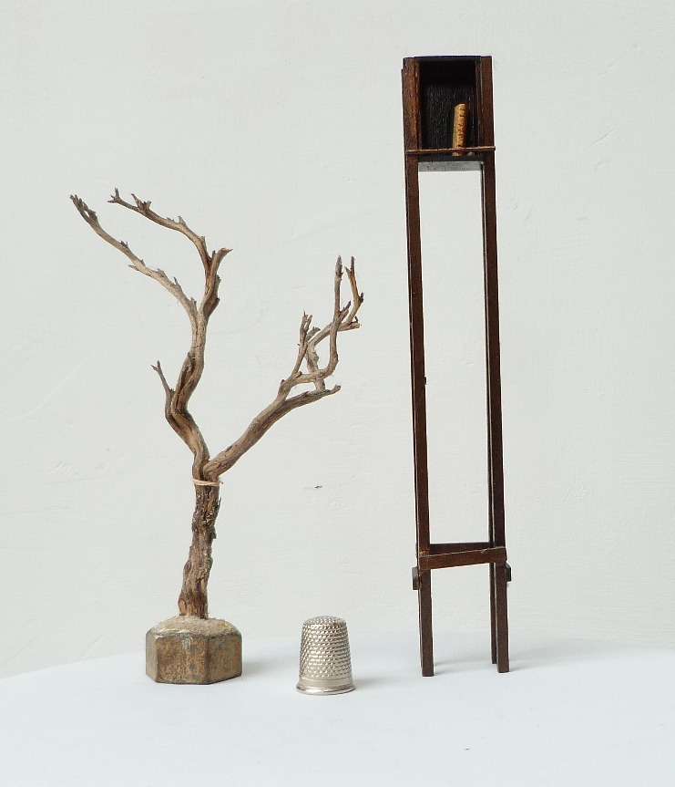 Mini-bibliothèque contenant un mini-livre accompagnée d' un arbre mort.