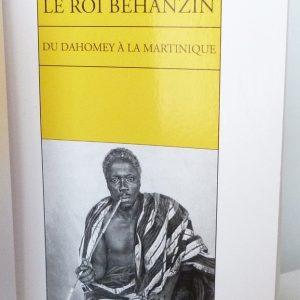 """Demi-cuir vert, collé à celui-ci 2 rectangles superposés jaune et rouge, le tout représentant à droite ou à gauche le drapeau béninois. Tranchefile tricolore reprenant le drapeau béninois que l'on retrouve aussi sur la tranche de tête. Une de couverture de : """"Le roi Béhanzin. Du Dahomey à la Martinique."""""""