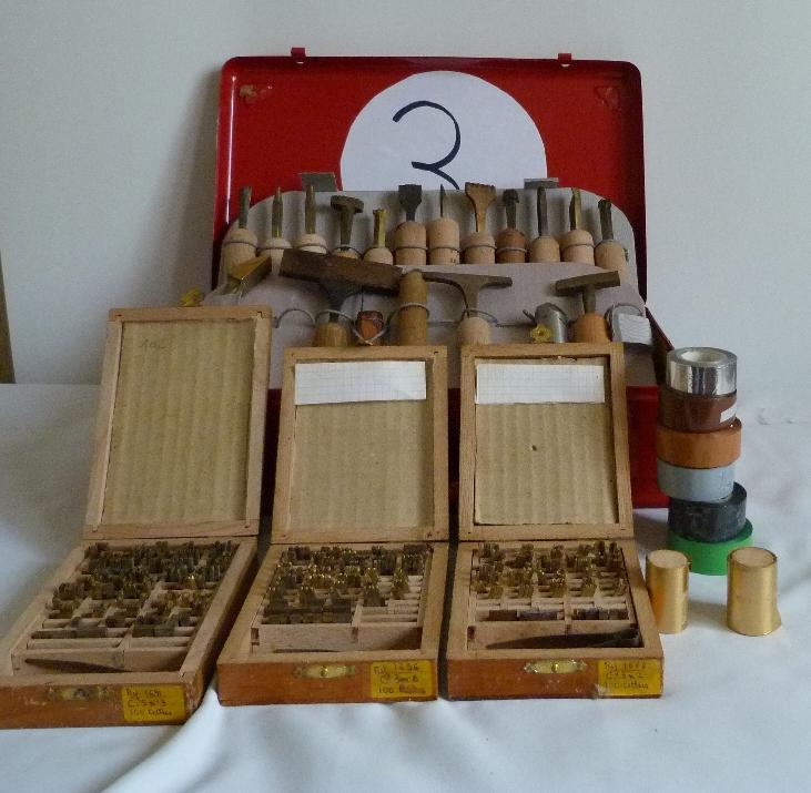 Fleurons, composteurs et polices de caractères.5 valises rouges en fer contenant le matériel dont j'ai besoin pour faire les décors de la reliure.