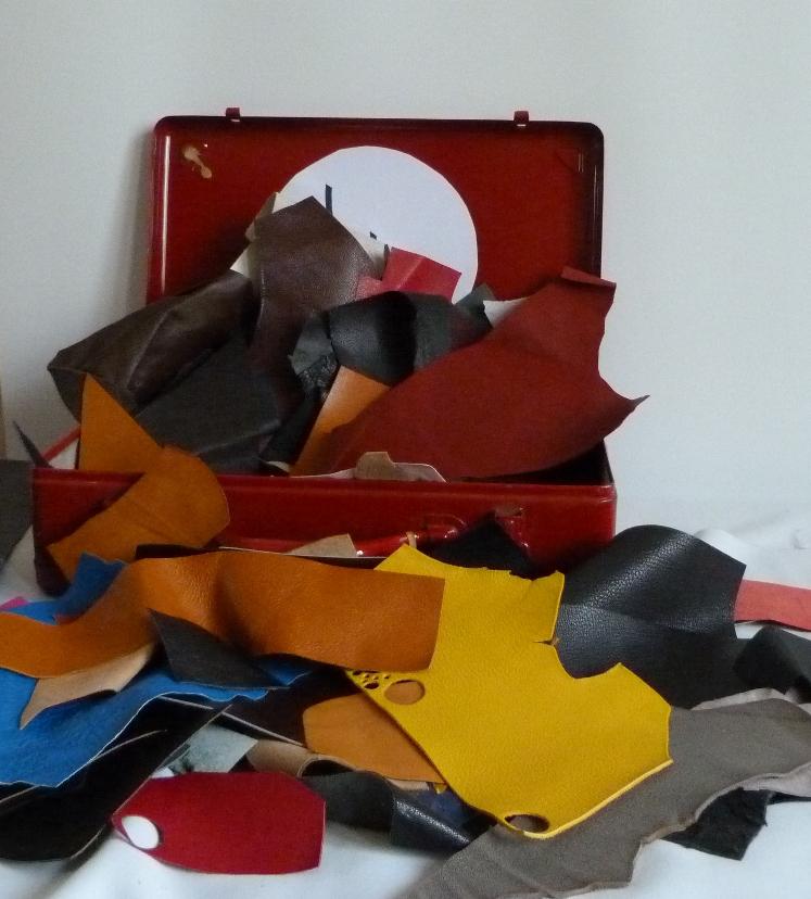 Chutes de cuir. 5 valises rouges en fer contenant le matériel dont j'ai besoin pour faire les décors de la reliure.