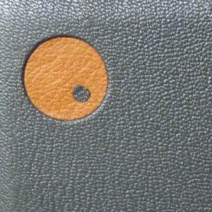 zoom reliure : incrustation d'un disque cuir jaune et point gris intérieur