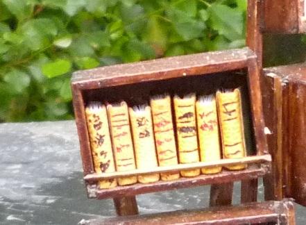 Mini-livres jaunes. Mini-bibliothèque en balsa sur pilotis. Chaque élement regroupe des livres de même nature, en général : couleur.