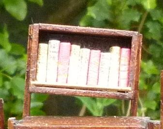 Mini-livres or. Mini-bibliothèque en balsa sur pilotis. Chaque élement regroupe des livres de même nature, en général : couleur.