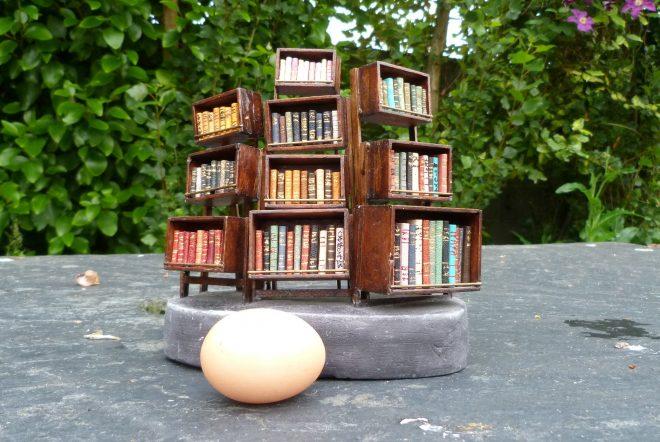 Avec un oeuf pour dimentionner. Mini-bibliothèque en balsa sur pilotis. Chaque élement regroupe des livres de même nature, en général : couleur.