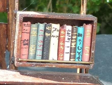 Mini-livres variés. Mini-bibliothèque en balsa sur pilotis. Chaque élement regroupe des livres de même nature, en général : couleur.