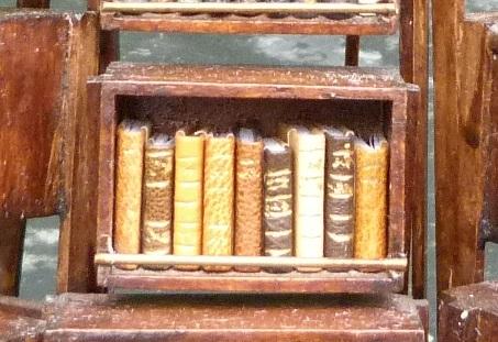Mini-livres marrons-Mini-bibliothèque en balsa sur pilotis. Chaque élement regroupe des livres de même nature, en général : couleur.