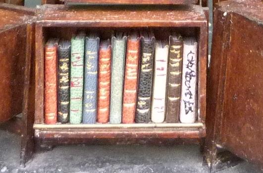 Mini-livres variés-Mini-bibliothèque en balsa sur pilotis. Chaque élement regroupe des livres de même nature, en général : couleur.