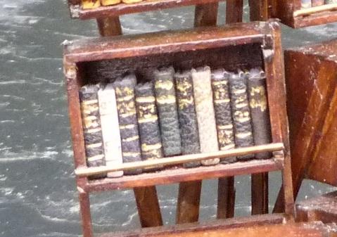 Mini-livres noirs.Mini-bibliothèque en balsa sur pilotis. Chaque élement regroupe des livres de même nature, en général : couleur.