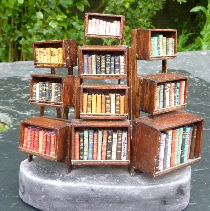 Vue d'ensemble. Mini-bibliothèque en balsa sur pilotis. Chaque élement regroupe des livres de même nature, en général : couleur.