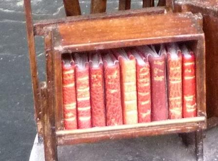 Mini-livres rouges.Mini-bibliothèque en balsa sur pilotis. Chaque élement regroupe des livres de même nature, en général : couleur.