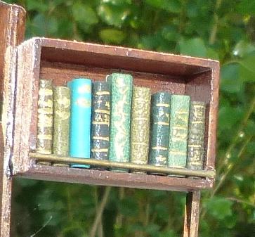 mini-livres verts.Mini-bibliothèque en balsa sur pilotis. Chaque élement regroupe des livres de même nature, en général : couleur.