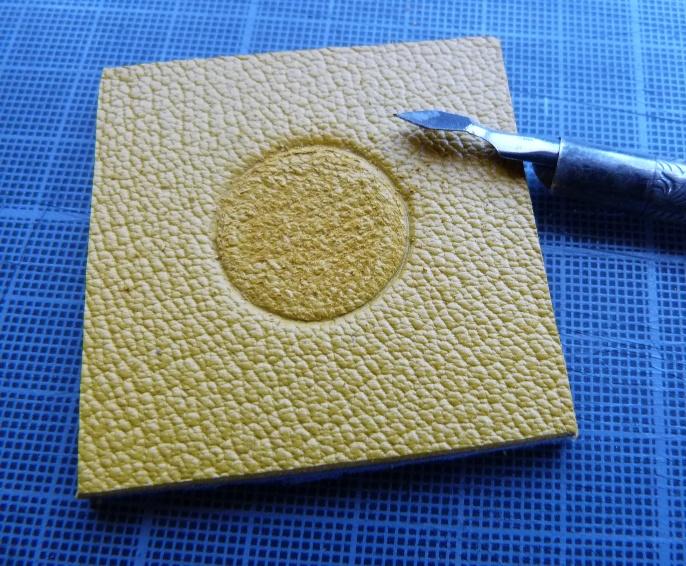 Gratage du cuir avant collage. Les deux options pour obtenir les ballons pour le décor de la reliure.