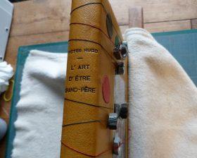 Dos du livre avec du fil de lin lestés aux deux extrémités de 2 écrous pour simuler les filets.