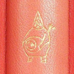 Silhouette du père Ubu en or sur fond rouge.