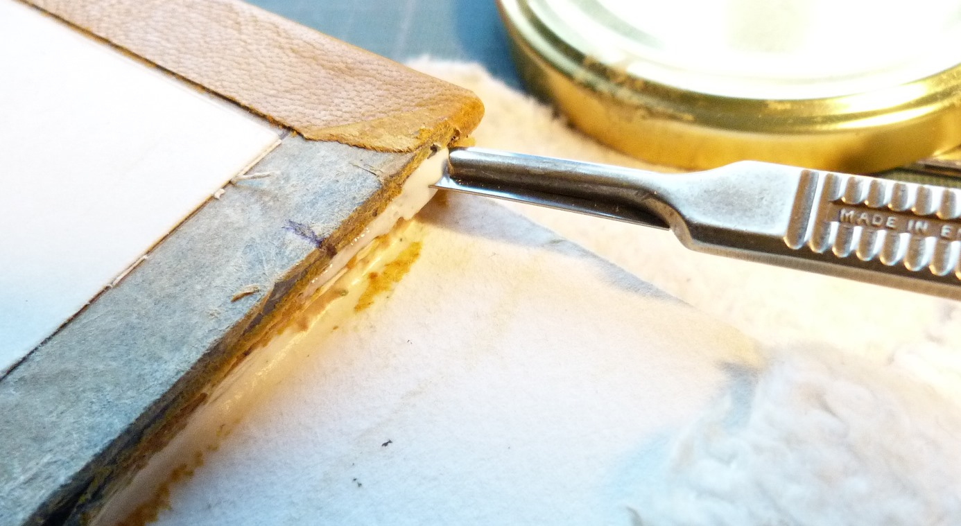 Insertion de la colle entre le cuir et le carton grace au scalpel.