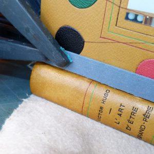Mise en presse du livre avec des pinces pour le recollage.