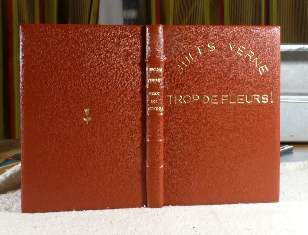 """Trop de fleurs de Jules Verne, plein-cuir-rouge, titre et décor à l'or fin, ajout de """"!"""" et d'une fleur."""