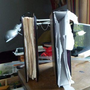 fabrication d'un étui bordé : la reliure est sortie de l'étui et le papier de soie n'est pas encore retiré