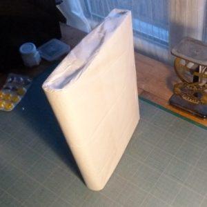 Fabrication d'une chemise, livre et chemise enveloppées de papier de soie.